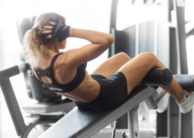 Athletic fitness woman do crunches on a bench in the gym